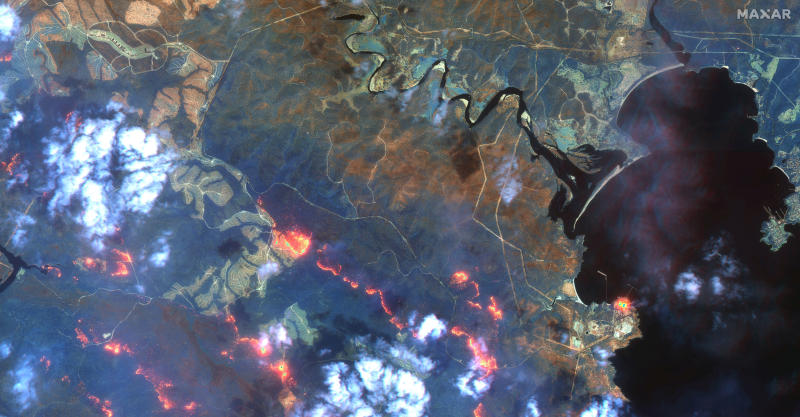 This satellite photo provided by Maxar Technologies shows wildfires spreading in the area south of Eden and Twofold Bay, shown in black, in New South Wales state of Australia, Sunday, Jan. 12, 2020. (Satellite image ©2020 Maxar Technologies via AP)