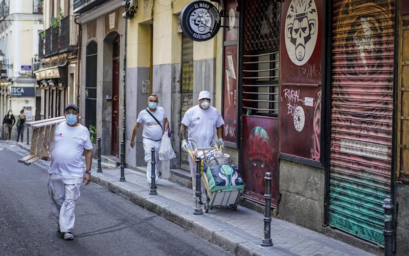 Construction workers walk down a street in the Lavapies neighborhood of Madrid, Spain, on Tuesday, Sept. 22, 2020. - Paul Hanna/Bloomberg