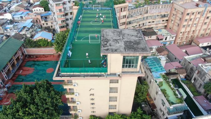 Foto udara pada 17 September 2020 menunjukkan lapangan olahraga di atas gedung Sekolah Menengah No.10 Guangzhou, China. Lapangan olah raga tersebut memiliki instalasi yang diperlukan seperti jaring pelindung, rumput sintetis, alat penerangan, dan sebagainya, di bagian atap gedung mereka. (Xinhua/Den