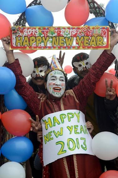 Indian revellers hold placards in Amritsar on December 31, 2012. Sydney will kick off a wave of dazzling firework displays welcoming in 2013, from Dubai to Moscow and London, with long-isolated Yangon joining the global pyrotechnics for the first time. AFP PHOTO/ NARINDER NANU