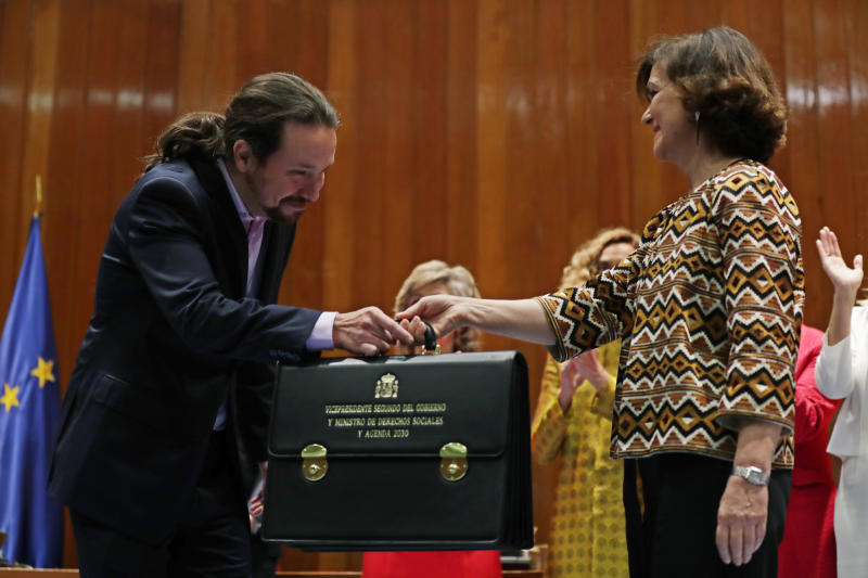 Podemos (United We Can) leader Pablo Iglesias, left, receives his ministerial briefcase from First Deputy Prime Minister Carmen Calvo in Madrid, Spain, Monday, Jan. 13, 2020. Iglesias will be one of four deputy prime ministers and in charge of social rights and sustainable development after a total of 22 ministers took their oaths in Spain's center to far left-wing coalition administration, a first in a country once dominated by two main parties taking turns in power. (AP Photo/Manu Fernandez)