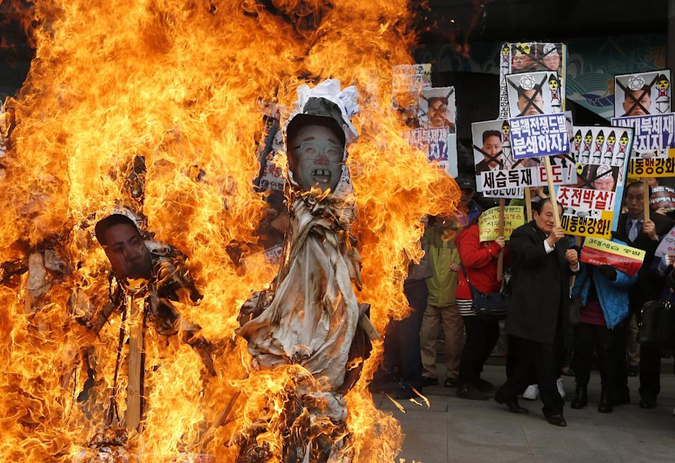 South Korean protesters burn effigies of North Korean leader Kim Jong-Un, and late leaders Kim Jong Il and Kim Il Sung at an anti-North Korea protest on the birthday of Kim Il Sung in Seoul, South Korea Monday, April 15, 2013. South Korea's defense minister, Kim Kwan-jin, told a parliamentary committee in Seoul on Monday that North Korea remains ready to launch a missile from its east coast, though he declined to disclose how he got the information.  (AP Photo/Kin Cheung)