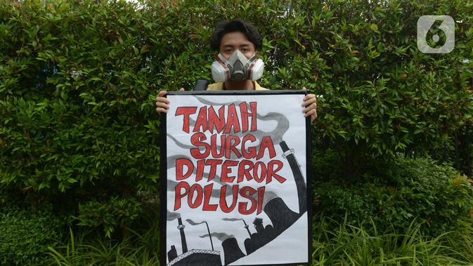 Aktivis lingkungan hidup menunjukkan spanduk bertuliskan 'Tanah Surga Diteror Polusi' saat berjalan kaki menuju Taman Aspirasi di Istana Merdeka, Jakarta, Jumat (29/11/2019). Aktivis meminta pemerintah segera mendeklarasikan perubahan iklim yang semakin kritis. (merdeka.com/Imam Buhori)