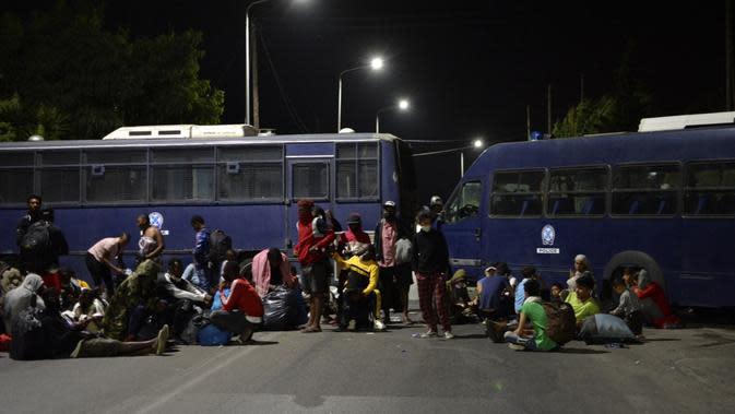 Pengungsi dan migran mencoba mencapai pelabuhan Mytilene saat polisi memblokir jalan saat terjadi kebakaran di kamp pengungsi Moria di timur laut pulau Aegean Lesbos, Yunani, Rabu (9/9/2020). Otoritas Yunani belum dapat mengungkap penyebab pasti terjadinya kebakaran. (AP Photo/Panagiotis Balaskas)