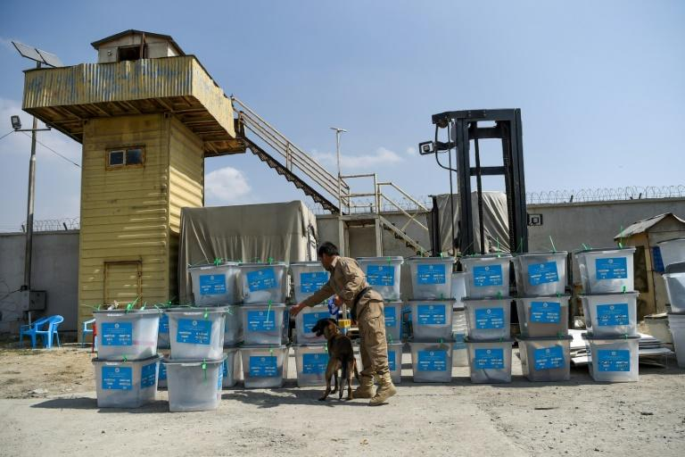 A sniffer dog checks election ballot boxes for explosives after they were unloaded from a truck at a warehouse in Kabul in September 2019