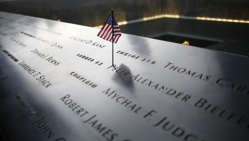 An American flag stands amongst names on the 9/11 memorial before the start of the 15th anniversary memorial service.