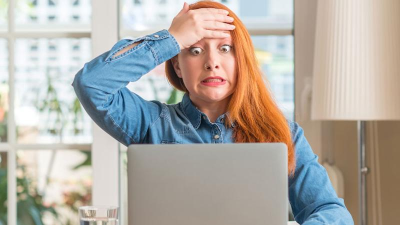 Shocked stressed young woman looking at laptop screen