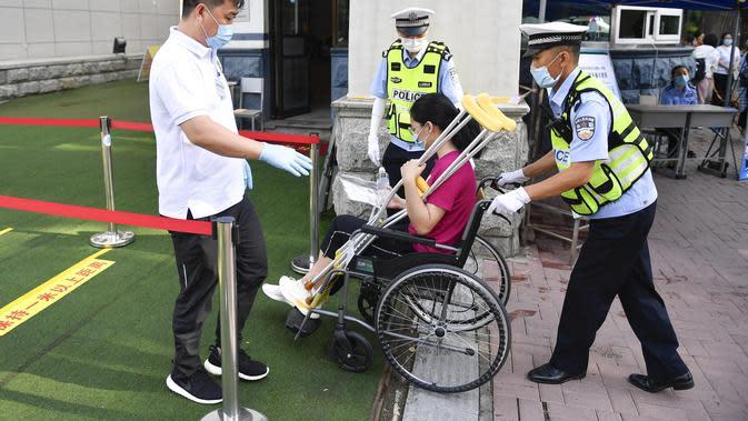 Seorang staf membantu peserta penyandang disabilitas memasuki lokasi ujian masuk perguruan tinggi di sekolah menengah atas di Changchun, ibu kota Provinsi Jilin, China timur laut (7/7/2020). Ujian masuk perguruan tinggi nasional China tahun ini telah dimulai pada Selasa (7/7). (Xinhua/Xu Chang)