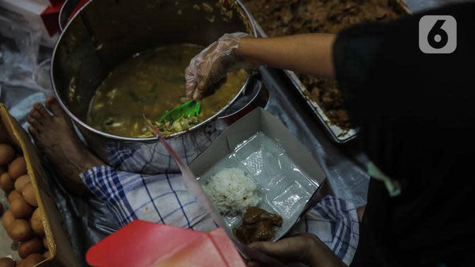 Petugas Taruna Siaga Bencana (Tagana) menyiapkan nasi kotak di Dapur Umum Kementerian Sosial Peduli Dampak Covid-19 di Kompleks Gedung Konvensi Taman Makam Pahlawan Nasional-Utama, Kalibata, Jakarta, Rabu (8/4/2020). Dapur umum ini dibuka sejak Senin, 6 April 2020 lalu. (Liputan6.com/Faizal Fanani)