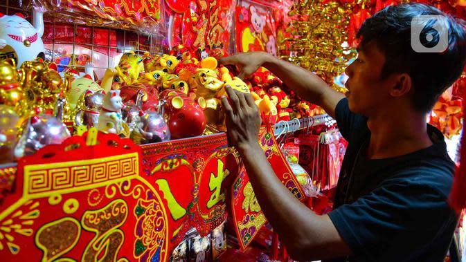 Pedagang menata pernak-pernik Imlek yang dijual di kawasan Glodok, Jakarta, Senin (13/1/2020). Menyambut tahun baru Imlek pada 25 Januari mendatang, penjualan pernak-pernik imlek dijual dengan harga Rp 5ribu hingga jutaan rupiah per buah tergantung jenis. (merdeka.com/Arie Basuki)