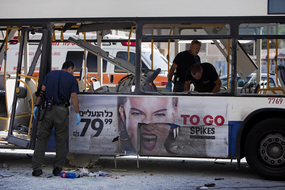Israeli police officers examine a blown up bus at the site of a bombing in Tel Aviv, Israel, Wednesday, Nov. 21, 2012. A bomb ripped through an Israeli bus near the nation's military headquarters in Tel Aviv on Wednesday, wounding at several people, Israeli officials said. The blast came amid a weeklong Israeli offensive against Palestinian militants in Gaza. (AP Photo/Oded Balilty)