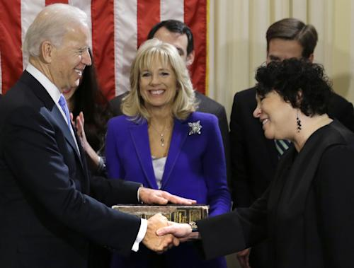 Vice President Joe Biden, with his wife Jill Biden, center, holding the Biden Family Bible, shakes hands with Supreme Court Justice Sonia Sotomayor after taking the oath of office during an official ceremony at the Naval Observatory, Sunday, Jan. 20, 2013, in Washington. (AP Photo/Carolyn Kaster)