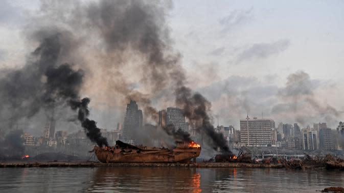 Sebuah kapal besar yang terbakar setelah ledakan besar di pelabuhan Kota Beirut, Lebanon (5/8/2020). Kapal besar tersebut terangkat ke daratan setelah dua ledakan besar menghantam Beirut pada Selasa (4/8/2020) lalu. (AFP Photo)