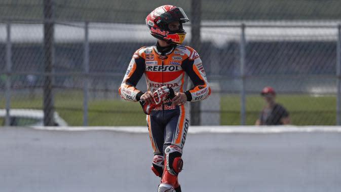 Marc Marquez harus mendapatkan bantuan dari marshal (petugas balapan) menuju podium karena motor yang ditungganginya kehabisan bensin setelah finis di MotoGP Inggris 2019. (AFP/ Adrian Dennis)