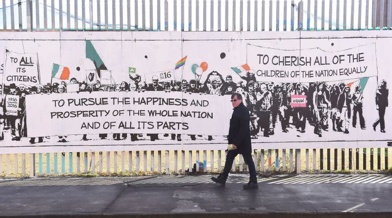 FILE PHOTO: A man walks past a mural consisting of quotes from the Irish Proclamation marking the 100 year anniversary of the Irish Easter Rising in Dublin, Ireland