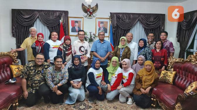 Konsulat Jenderal Republik Indonesia di Kuching, Yonny Tri Prayitno dan Kepala BKKBN, Hasto Wardoyo, berfoto bersama para bidan yang bertugas saat bakti sosial pemasangan alat kontrasepsi kepada PMI (Foto: Aditya Eka Prawira/Liputan6.com)