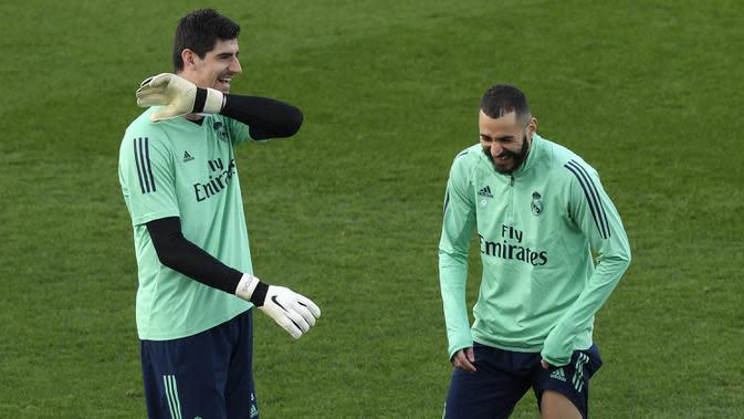 Kiper Real Madrid, Thibaut Courtois (kiri) dan penyerang Karim Benzema tertawa selama sesi latihan tim di Valdebebas di Madrid (AP Photo/Oscar Del Pozo)