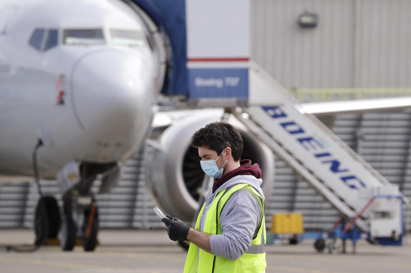 A worker walks past a Boeing 737 MAX jet at a Boeing airplane manufacturing plant Wednesday, April 29, 2020, in Renton, Wash. Boeing says it will cut about 10% of its workforce and slow production of planes as it deals with the ongoing grounding of its best-selling plane and the coronavirus pandemic. With air travel falling sharply because of the virus, airlines have delayed orders and deliveries of new planes, reducing Boeing's revenue. (AP Photo/Elaine Thompson)