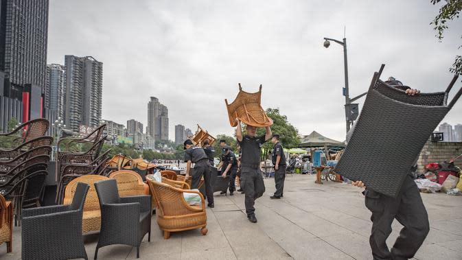 Para petugas membantu sejumlah pedagang yang tinggal di dekat tepi Sungai Yangtze memindahkan barang-barang mereka ke tempat yang lebih aman di Jalan Nanbin, Kota Chongqing, China barat daya (18/8/2020). (Xinhua/Huang Wei)