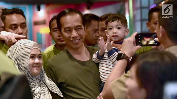 Warga foto bersama Presiden Joko Widodo dan cucunya Jan Ethes di mal Botani Square, Bogor, (8/12). Presiden tampil berkaos hijau dengan celana jins dan sepatu sneakers. sang cucu mengenakan kaos garis-garis. (Liputan6.com/HO/Biro Pers Setpres)