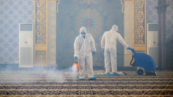 Pekerja mengenakan APD melakukan semprotan desinfektan di sebuah masjid di Bandar Seri Begawan, Brunei. (AFP)
