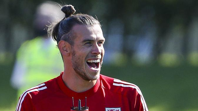 Pemain Timnas Wales, Gareth Bale, tertawa saat mengikuti latihan jelang laga UEFA Nations League di Hensol, South Wales, Senin (31/8/2020). Wales akan berhadapan dengan Finlandia. (AFP/Geoff Caddick)