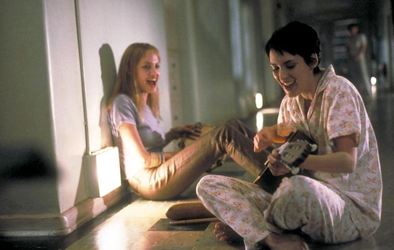 """376554 03: After friend and fellow patient Polly lands herself in solitary, Lisa (Angelina Jolie, left) and Susanna (Winona Ryder) serenade her in the Columbia Pictures presentation, """"Girl, Interrupted."""" Photo credit: Suzanne Tenner 1999 Columbia Pictures, Inc"""