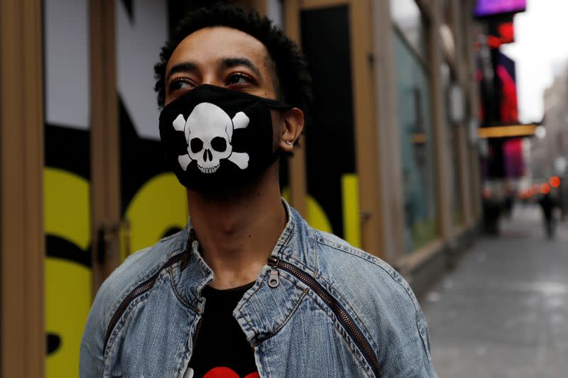 FILE PHOTO: A man wears a protective mask decorated with skull and crossbones design as he walks in midtown Manhattan during the coronavirus outbreak in New York