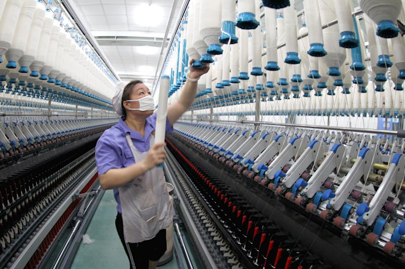 XUCHANG, CHINA - MAY 22: A worker checks threads running through a machine at a textile mill on May 22, 2019 in Xuchang, Henan Province of China. China's value-added industrial output expanded 5.4 percent year on year in April, data released by the National Bureau of Statistics (NBS) on May 15. (Photo by VCG/VCG via Getty Images)