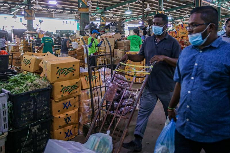 Workers are seen at the Kuala Lumpur Wholesale Market in Selayang June 24, 2020. ― Picture by Hari Anggara