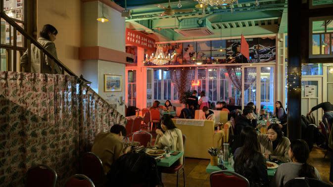 Suasana aktivitas pengunjung Pyeongyang Bar di Distrik Hongdae, Seoul, Korea Selatan, Jumat (10/1/2020). Pyeongyang Bar dihiasi berbagai slogan dan propaganda palsu seperti yang ada di Korea Utara. (ED JONES/AFP)
