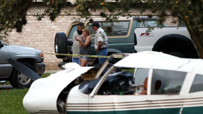 Sejumlah warga terlihat di lokasi kecelakaan pesawat di daerah Houston di Texas, Amerika Serikat (AS) (28/7/2020). Dua orang terluka ketika pesawat kecil itu jatuh pada Selasa (28/7) pagi di sebuah permukiman di Houston. (Xinhua/Steven Song)
