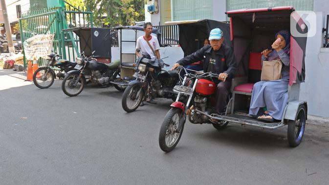 Penumpang menaiki ojek becak motor di salah satu perumahan di kawasan Meruya, Jakarta, Selasa (19/11/2019). Pesatnya perkembangan teknologi transportasi seperti ojek berbasis aplikasi, mengakibatkan keberadaan becak motor di Ibukota hampir punah. (Liputan6.com/Herman Zakharia)