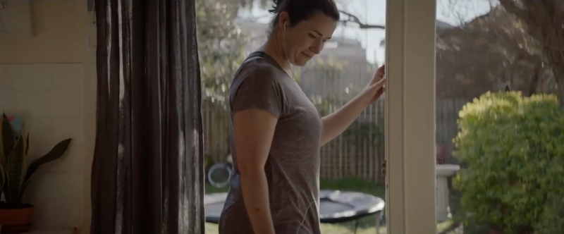 A woman in workout clothing in a Medibank commercial. She's returning to her family after exercising. The ad's been criticised for shaming mums.