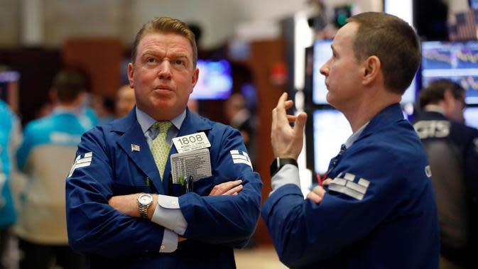 Spesialis Michael Mara (kiri) dan Stephen Naughton berunding saat bekerja di New York Stock Exchange, AS, Rabu (11/3/2020). Bursa saham Wall Street anjlok pada akhir perdagangan Rabu (11/3/2020) sore waktu setempat setelah WHO menyebut virus corona COVID-19 sebagai pandemi. (AP Photo/Richard Drew)