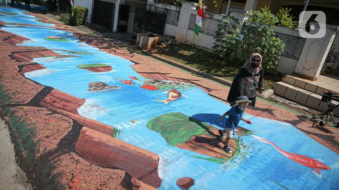 Warga melintas di atas jalan yang telah dilukis mural di Jalan Keuangan, Cilandak, Jakarta, Rabu (26/8/2020). Museum Basoeki Abdullah bekerjasama dengan Perupa Jakarta Raya membuat mural dengan memanfaatkan ruang publik di sepanjang jalan menuju museum Basoeki Abdullah. (Liputan6.com/Faizal Fanani)