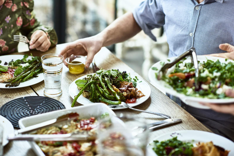 Close up shot of people sitting at dining room table with plates of vegetables and salad, person serving guests at dinner party, man about to pour dressing on his meal