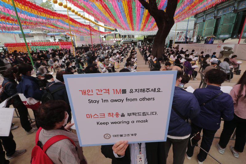 A Buddhist believer holds a notice about precautions against the new coronavirus during a service to pray for overcoming the COVID-19 outbreak and to celebrate Buddha's birthday at the Chogyesa temple in South Korea, Thursday, April 30, 2020. (AP Photo/Ahn Young-joon)