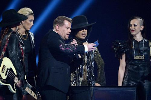 CAPTION ADDS THE NAMES OF THE GROUP 3RDEYEGIRL Host James Corden, centre, takes a picture onstage with US recording artist Prince and group 3rdeyegirl Donna Grantis, Hannah Ford and Ida Nielsen, during at the BRIT Awards 2014 at the O2 Arena in London on Wednesday, Feb. 19, 2014. (Photo by Jon Furniss/Invision/AP)