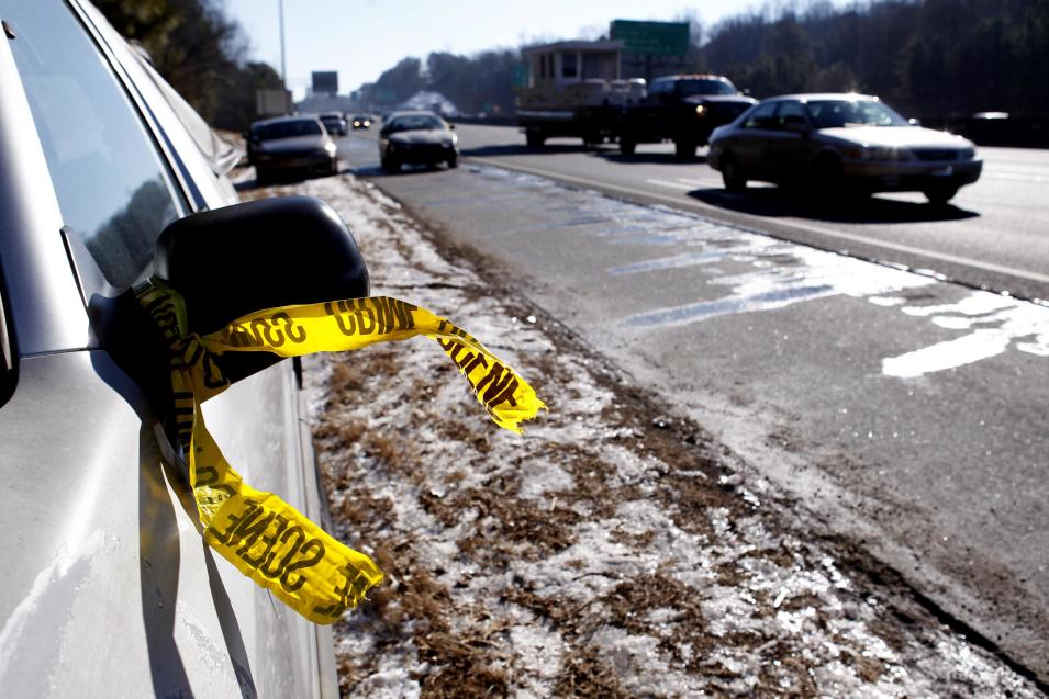 A car marked by crime tape to show it was checked sits abandoned on the side of the road on the Perimeter in Atlanta, Georgia