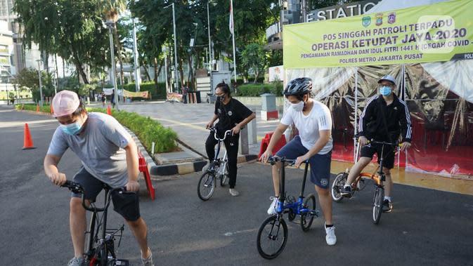 Sejumlah pesepeda beraktivitas di kawasan Bundaran HI, Jakarta, Minggu (24/5/2020). Adanya PSBB serta Hari Raya Idul Fitri 1441 H dimanfaatkan sebagian warga untuk bersepeda di jalan protokol yang sepi dibanding hari biasa. (Liputan6.com/Immanuel Antonius)