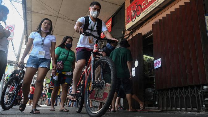 Karyawan toko kelontong mengendarai sepeda yang baru dibeli dalam perjalanan ke Manila pada 20 Mei 2020. Alat transportasi umum yang masih beroperasi dalam kapasitas terbatas membuat warga Filipina beralih ke sepeda saat berakhirnya masa karantina dan dimulainya periode New Normal. (Ted ALJIBE/AFP)
