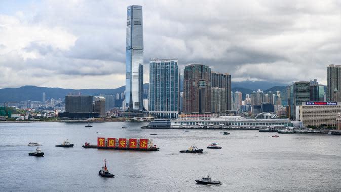"Kapal tongkang dengan spanduk bertuliskan ""Rayakan Hukum Keamanan Nasional"" berlayar di Victoria Harbour pada peringatan 23 tahun penyerahan Hong Kong dari Inggris ke China di Hong Kong, Rabu (1/7/2020). Hong Kong menandai 23 tahun penyerahan dari Inggris ke Cina pada 1 Juli. (Anthony WALLACE/AF"