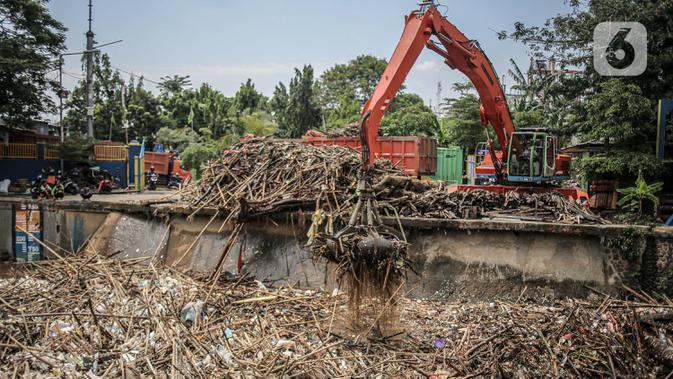 Pekerja kebersihan mengangkat sampah yang menumpuk di pintu air Manggarai, Jakarta, Selasa (22/9/2020). Tingginya curah hujan membuat kiriman sampah menumpuk di pintu air Manggarai. (Liputan6.com/Faizal Fanani)