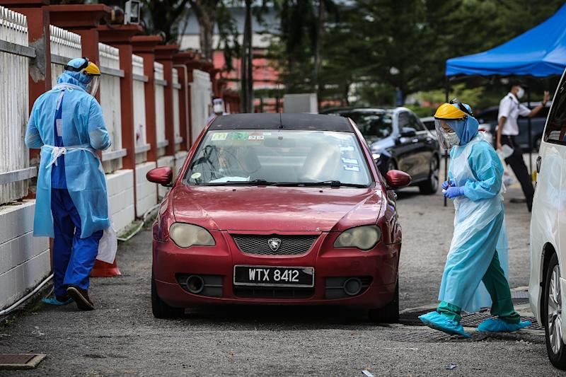 A health worker in protective suit swabs a driver's mouth at a drive-through testing site for Covid-19 at KPJ Damansara Specialist Hospital in Petaling Jaya March 28, 2020. — Picture by Yusof Mat Isa