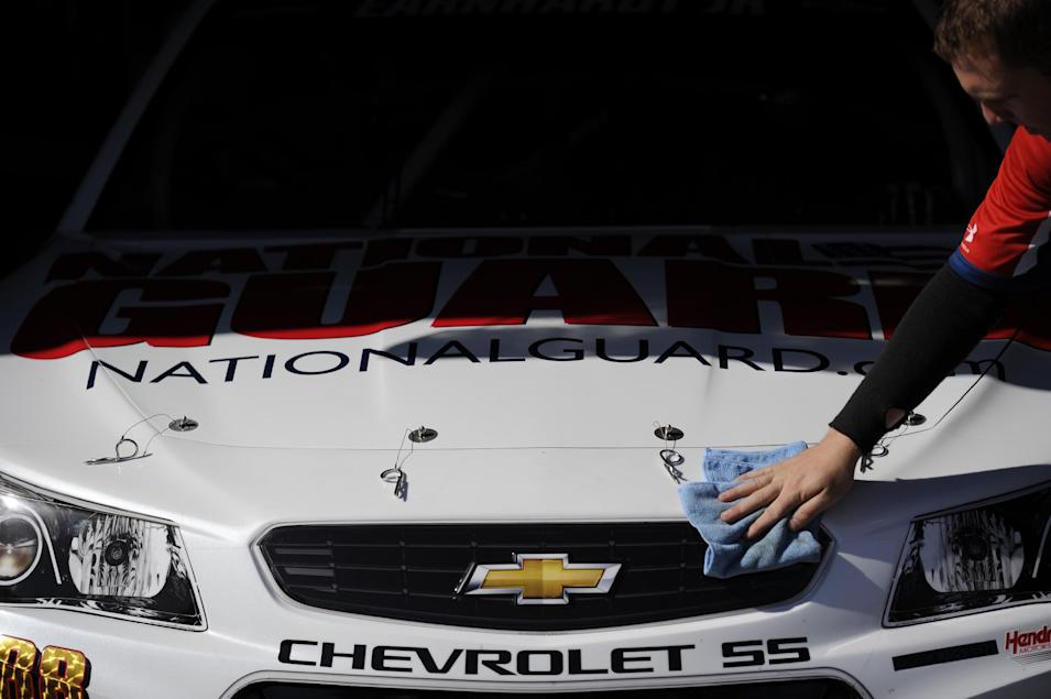 A pit crew member wipes down Dale Earnhardt Jr.'s car before practice for the NASCAR Sprint Cup series auto race, Saturday, May 31, 2014, at Dover International Speedway in Dover, Del. (AP Photo/Nick Wass)