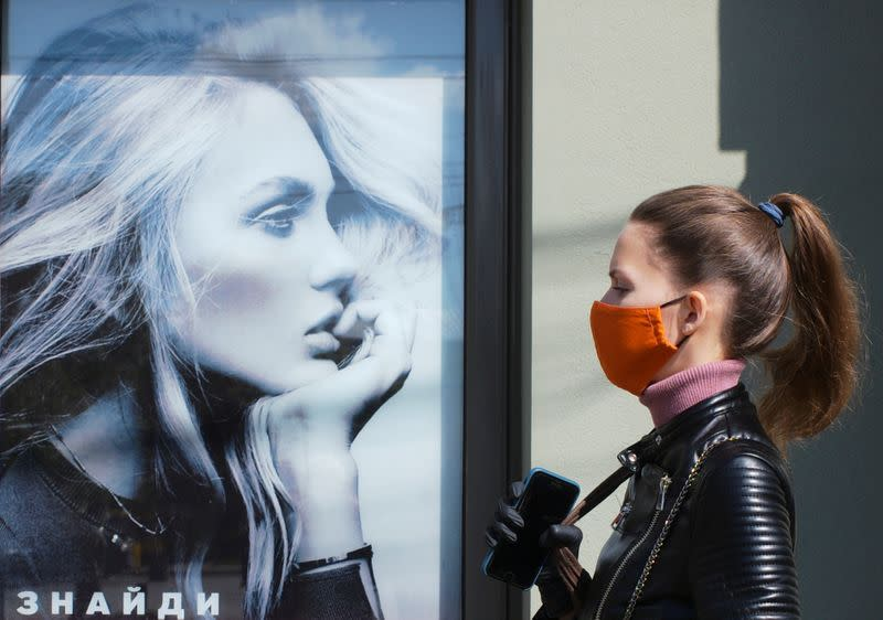 FILE PHOTO: A woman wearing a protective face mask walks near an advertising poster in Kiev