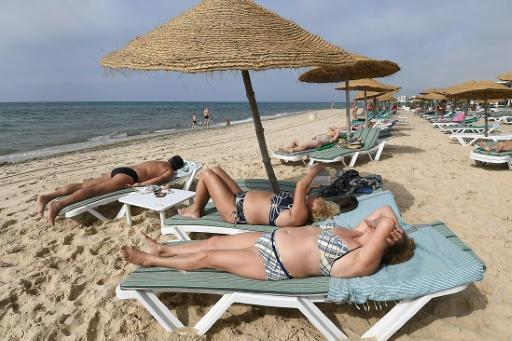 Tourists sunbathe on a private beach near a hotel in Nabeul on July 1, 2018