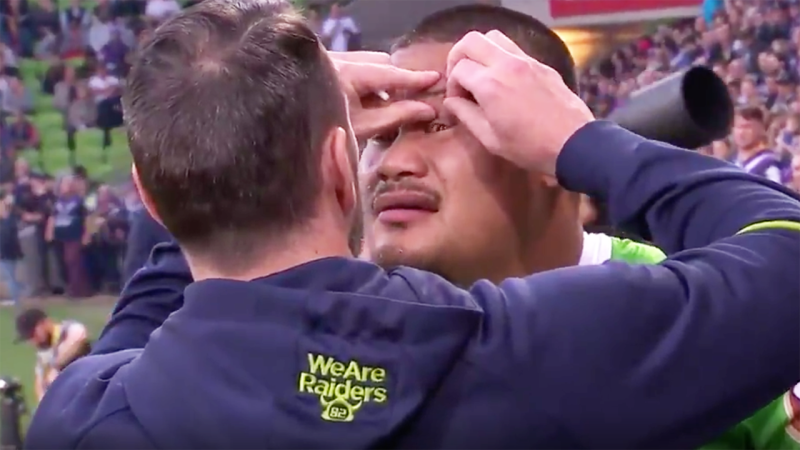 A Canberra Raiders trainer tends to Joey Leilua after he was struck by a loose fragment from a firework moments prior to the NRL final against the Melbourne Storm at AAMI Park. Picture: Channel 9