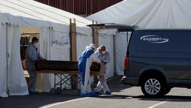 Relawan memasukkan peti mati berisi jenazah korban COVID-19 ke dalam van untuk dimakamkan, di halaman parkir Central Jamis Mosque Ghamkol Sharif di Birmingham, Inggris pada 24 April 2020. Masjid itu mengubah tempat parkirnya menjadi kamar mayat sementara untuk korban virus corona. (AP/Matt Dunham)